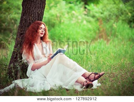 Beautiful ginger woman sitting under the tree and reading a book