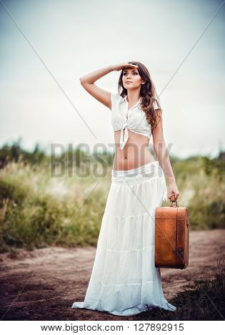 Beautiful young woman with suitcase in hands stands on a rural road