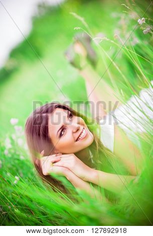 Cheerful beautiful young woman lying among the grass and flowers