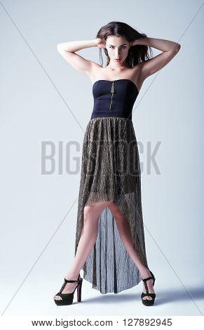 Studio fashion shot: a beautiful young woman in dress