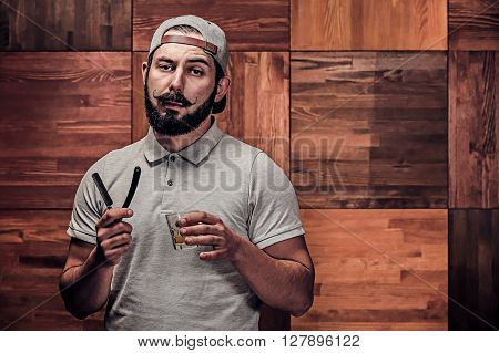 Bearded hipster with straight edge razor and whiskey on a wooden texture in barbershop. Free space to fill, text.