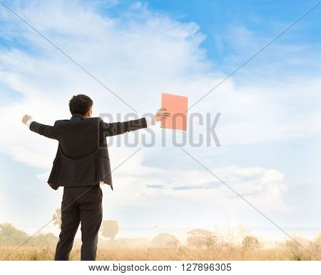 Warm tone. Victory Business man standing on the field looking to the blue sky white cloud.
