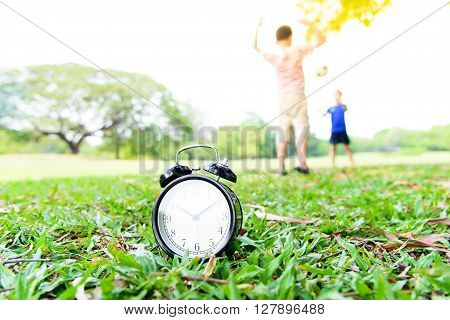 Black Alarm Clock And Boy Play In The Park