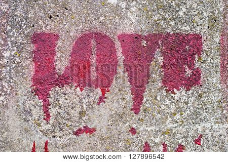 Red paint label spray love on concrete wall