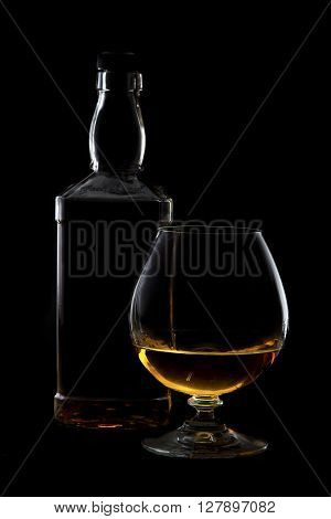 Cognac glass and bottle with brandy with rim lighting on black background