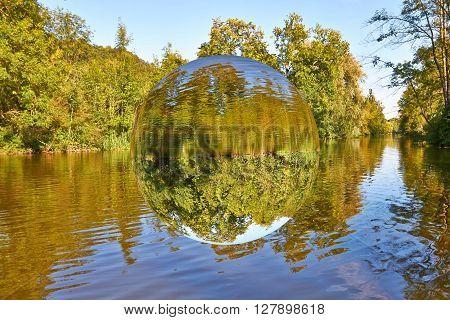 About a romantic river floats a transparent sphere.