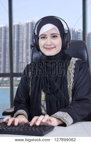 Beautiful middle eastern businesswoman working in the office with headphones and typing on the keyboard