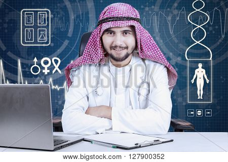 Arabic male doctor smiling at the camera while sitting in the laboratory and folded his hand with laptop on desk
