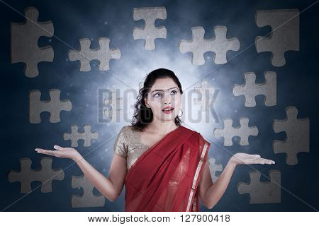 Portrait of pretty Indian woman wearing sari clothes and looks confused to connect puzzles