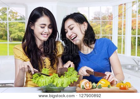 Photo of two happy Asian women cooking vegetables salad in the kitchen at home