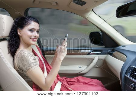 Pretty Indian businesswoman using mobile phone in the car while wearing sari clothes and smiling at the camera