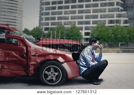 Angry person speaking on the cellphone while sitting in front of a broken car after traffic accident