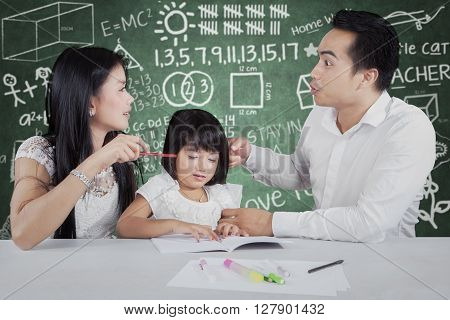 Picture of two young parents arguing while teaching their daughter to study with book on the table