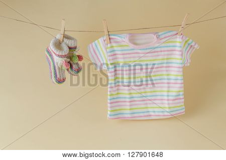 Baby laundry hanging on a clothesline beige background