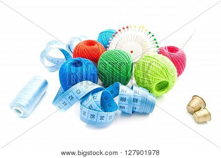 Pins, Thimbles, Meter And Thread On White