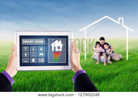 Picture of hands holding tablet with smart house controller applications on the screen. Shot with young man and his children reading book under a house symbol