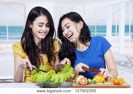 Portrait of two cheerful Asian girls with long hair cooking vegetables salad in the kitchen