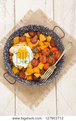 spanish country style meal with potato cherry tomato fried egg parsley and chorizo in a pan