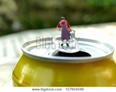 Miniature Cleaning Lady Carrying Heavy Bucket On Top Of Soda Can With Blurred Background. Business C