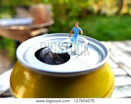 Miniature Workman Sitting On Top Of Soda Can With Blurred Background. Business Concept