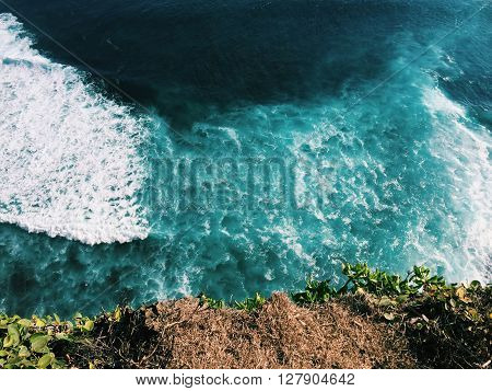 Ocean and rip curl view from abrupt cliff coast, Bali sea landscape, look down from the height, rip curl photo, surfing wave from above, Bali sea and surfing, high cliff and sea, jumping from cliff