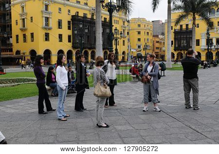 20 November 2010- Plaza de armas Lima Peru. Tourists standing on the Plaza de Armas near the Headquarters of the Caretas magazine.