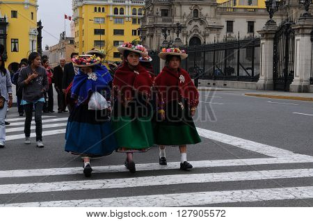 20 November 2010 - Lima Peru. Peruvian indigenous women are crossing the street near the Government palace in Lima Peru.