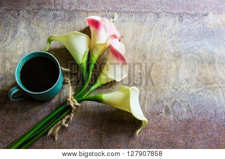 Calla Flowers And Cup Og Coffee On Rustic Table
