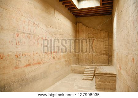 room with stone walls of egyptian temple with carved hieroglyphs and figures with ceremony procession of people with animals and food in Egypt Africa