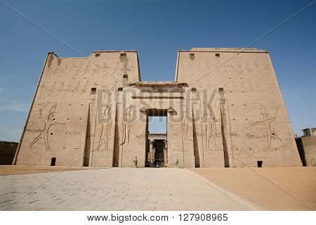 high wall front facade of Egyptian Edfu Temple of falcon god Horus with carving figures and hieroglyphs in Egypt Africa