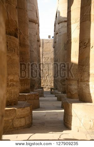 big stone columns and wall with carving figures and hieroglyphs in landmark Egyptian Karnak Temple public ancient monument declared a World Heritage by Unesco in Luxor Egypt Africa