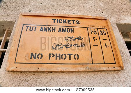 wooden placard with rates tickets and no photo in Egyptian Tut Ankh Amon tomb or Tutankhamun in landmark Kings Valley in Egypt Africa