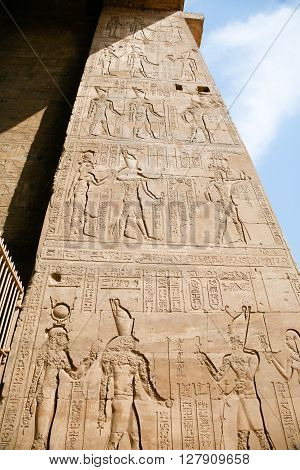 stone wall of Egyptian Edfu Temple of falcon god Horus with carving figures and hieroglyphs ceremony people priest pharaoh or king goddess or queen in Egypt Africa