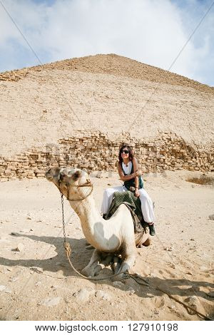 brunette tourist woman portrait sitting riding on white dromedary or arabic camel resting on desert next to Bent Pyramid in Dahshur Egypt Africa for Sneferu pharaoh