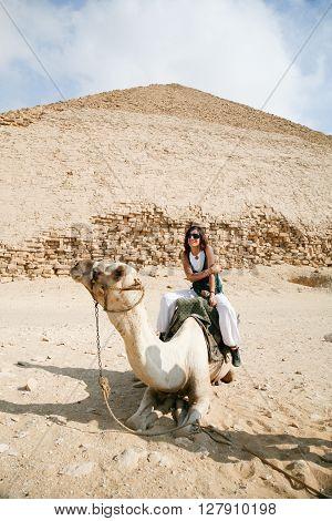brunette tourist woman portrait sitting riding on white dromedary or arabic camel resting on desert next to Bent Pyramid in Dahshur Egypt Africa for Sneferu pharaoh