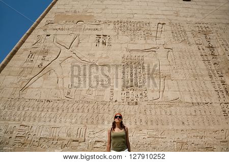 tourist woman in front of wall facade of landmark Egyptian Temple of Ramses or Ramesses III at Medinet Habu monument with carving figures and hieroglyphs in Luxor Egypt Africa