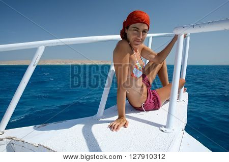woman scarf and bikini sitting on white bow of boat or yacht looking in Egyptian Red Sea blue ocean water next to Sharm al Sheij and Hurghada Egypt Africa