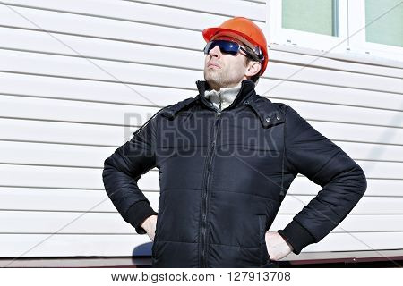 Worker on a construction site in winter looks and compares work done