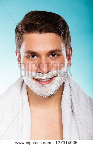 Young man with shaving cream foam and white towel. Handsome guy preparing to shave. Skin care and hygiene.