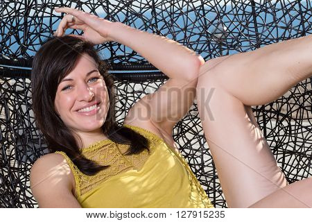 Portrait Of Beautiful Young Woman Relaxing On Sunny Day In Rattan Patio Swing Egg-chair