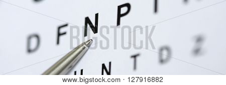Silver ballpoint pen pointing to letter in eyesight check table. Sight test and correction excellent vision or optician shop laser surgery alternative driver health certificate examination concept