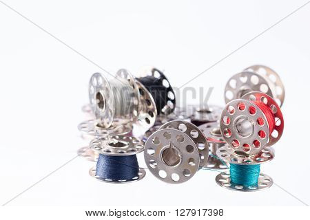 Messy metal thread bobbins isolated on white background