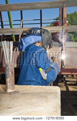 Woman welding wearing protective clothes and equipment