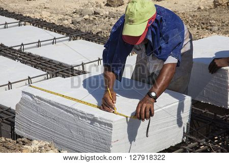 Worker Taking measures of an Iron framework and polyurethane  to build a foundation for a building
