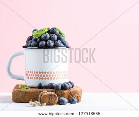 Fresh ripe blueberries in country style enamel mug on rustic wooden board over pastel pink background, selective focus, copy space