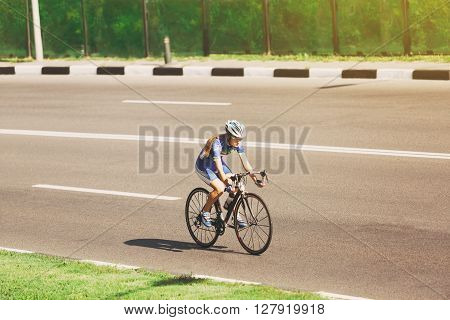Female sportsman cyclist riding racing bicycle. Woman cycling on countryside summer road or highway. Training for triathlon or cycling competition.