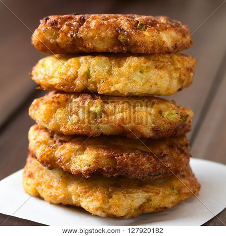 Rice patties or fritters made of cooked rice carrot onion garlic and celery stalks arranged in a pile photographed with natural light (Selective Focus Focus on the front of the patties)