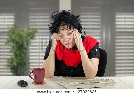 Unhappy middle-aged woman is sitting at white desk. The sad woman wears black dress and red scarf. There are maroon mug keyboard on desk and unfocused shutters as background. Horizontal indoors picture.