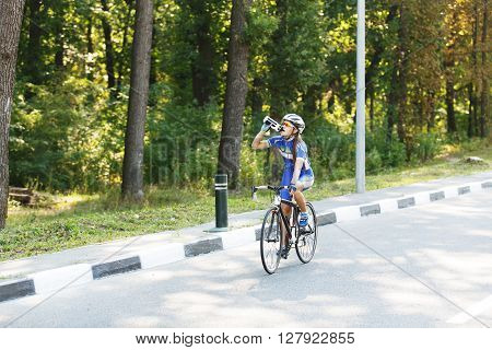Female sportsman cyclist drinks water from the bottle at the race. Riding racing bicycle. Break, stop at road.  Woman cycling on countryside summer road or highway. Triathlon or cycling competition.