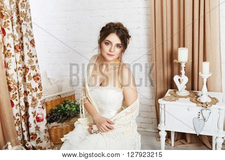 Wedding dress fashion. Beautiful young bride in vintage crochet shawl, shabby chic champagne color wedding dress. Rustic wedding dress at model, in decorated interior, studio shot, high key.